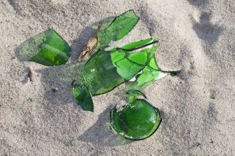 14126882-Broken-glass-in-beach-sand--Stock-Photo